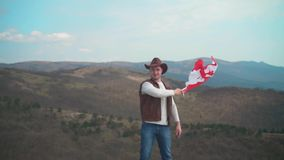 Ein Mann in einem Hut, eine Weste und eine Lederjacke und Jeans h?lt eine kanadische Flagge Flagge von Kanada entwickelt sich im  stock video