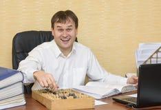 Ein Mann in einem lachenden Zeigen des Büros auf einen Abakus Lizenzfreies Stockbild