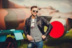 Ein Mann in einem Lederjacke- und Sonnenbrillelächeln stockfoto