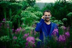 Ein Mann in einem Matrosen auf einer Blumenwiese stockfotografie