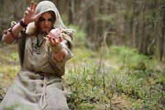 Ein Mann in einem Messrock wendet ein Ritual in einem dunklen Wald auf Stockfotos