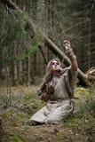 Ein Mann in einem Messrock wendet ein Ritual in einem dunklen Wald auf Lizenzfreies Stockbild