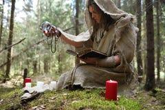 Ein Mann in einem Messrock wendet ein Ritual in einem dunklen Wald auf Stockfoto