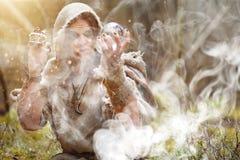 Ein Mann in einem Messrock wendet ein Ritual in einem dunklen Wald auf Lizenzfreie Stockfotos