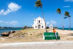 Ein Mann in einem orange T-Shirt betrachtet die Kirchenfestung von San Antonio auf Mosambik-Insel, mit drei Palmen auf Sand stockfotografie