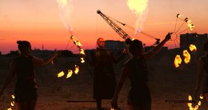 Ein Mann in einem Regenmantel mit zwei Flammenwerfern lässt heraus eine brennende Flammenstellung bei Sonnenuntergang auf dem San stock video