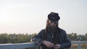 Ein Mann in einem Regenmantel und in einem Hut steht am Rand der Brücke und säubert sein großes Messer stock footage