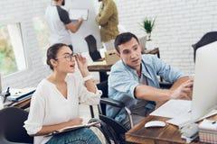 Ein Mann in einem Rollstuhl zeigt seinem Kollegen etwas auf Computer stockfotos