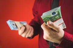 ein Mann in einem roten Hemd mit einer Karte h?lt in seiner Hand ein Pack von Rechnungen auf einem roten Hintergrund lizenzfreie stockbilder