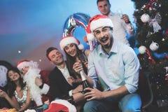 Ein Mann in einem Santa Claus-Hut öffnet eine Flasche Champagner Ein Mann ` s sitzen Freunde nahe bei ihm und einem Kerl, der als lizenzfreies stockbild