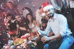 Ein Mann in einem Santa Claus-Hut öffnet eine Flasche Champagner Ein Mann ` s sitzen Freunde nahe bei ihm und einem Kerl, der als stockfotos