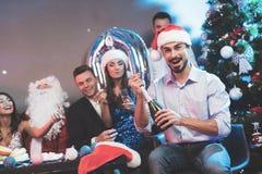 Ein Mann in einem Santa Claus-Hut öffnet eine Flasche Champagner Ein Mann ` s sitzen Freunde nahe bei ihm und einem Kerl, der als lizenzfreie stockfotos