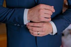 Ein Mann in einem schwarzen Anzug richtet seine Manschettenknöpfe gerade Lizenzfreie Stockfotografie