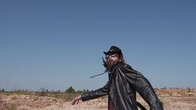 Ein Mann in einem schwarzen Mantel läuft durch die Wüste sich dreht herum und läuft vorwärts wieder stock video