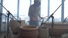 Ein Mann in einem Sweatshirt hebt Trommelstöcke für das Spielen auf Tongefäßen auf stock footage