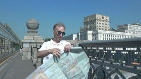 Ein Mann in einem weißen Hemd steht auf einer Brücke und betrachtet eine Papierkarte der Stadt stock video