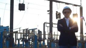 Ein Mann in einem weißen Sturzhelm und in schwarzen Gläsern steht gegen den Hintergrund eines Kraftwerks, sein Waffenkreuzkreuz,  stock video