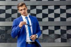 Ein Mann in einer blauen Klage gegen einen Hintergrund der dunklen modernen Architektur Stockfotografie