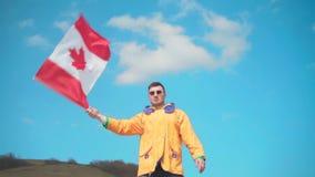 Ein Mann in einer gelben Jacke, in den Blue Jeans und in den Gläsern steht in den Bergen und bewegt die Flagge von Kanada von Sei stock video