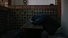 Ein Mann in einer Haube schläft am Tisch in der Stange stock video footage