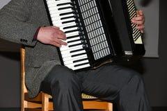 Ein Mann in einer Klage spielt das Akkordeon stockfoto