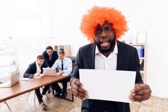 Ein Mann in einer Perücke kam zu einem Geschäftstreffen Lizenzfreie Stockfotos