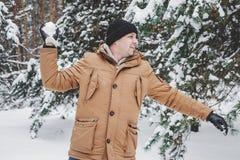 Ein Mann in einer Rotjacke wirft einen Schneeball im spielerischen Winterwald Lizenzfreies Stockbild