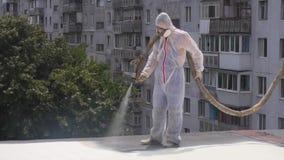 Ein Mann in einer speziellen Form auf dem Dach benutzt eine chemische Lösung und malt das Dach, isoliert das Dach stock footage