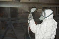 Ein Mann in einer wei?en Uniform wendet Farbe mit einer Farbspritzpistole auf einem Metallprodukt an stockbild