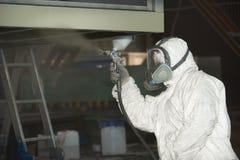 Ein Mann in einer wei?en Uniform wendet Farbe mit einer Farbspritzpistole auf einem Metallprodukt an lizenzfreies stockbild