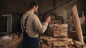 Ein Mann in einer Zimmereiwerkstatt mit einer Tablette und einem Stift zählt die Anzahl von den hölzernen Blöcken Jointer ist im  stock footage