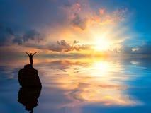 Ein Mann am einsamen Felsen im Ozean lizenzfreie stockfotos