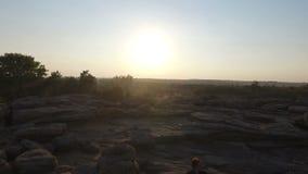 Ein Mann engagierte sich in der chinesischen Gymnastik, auf den Felsen bei Sonnenuntergang aerial stock video footage