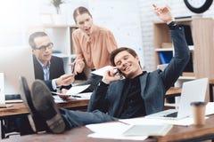 Ein Mann entspannt sich bei der Arbeit Er steht im Geschäftslokal still stockbilder