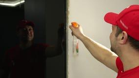Ein Mann, ein Erbauer in einer roten Kappe, sprüht Flüssigkeit auf schwarzen Glastüren stock video footage