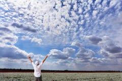 Ein Mann erfreute sich mit der Schönheit eines bewölkten Himmels Lizenzfreies Stockfoto