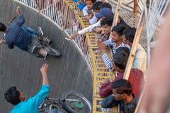 Ein Mann erreicht für die Spitzen, die von den Zuschauern beim Reiten der Wand des Todes an einem f gebaumelt werden lizenzfreie stockfotografie