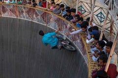 Ein Mann erreicht für die Spitzen, die von den Zuschauern beim Reiten der Wand des Todes an einem f gebaumelt werden lizenzfreie stockbilder