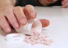 Ein Mann erreicht für Tabletten oder Pillen über einer Tabelle stockfotografie