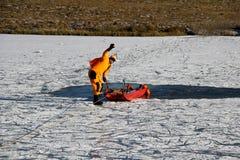 Ein Mann ertrinkt im eisigen Wasser Ein Mann in einer speziellen Klage ertrinkt in einem gefrorenen See stockfotos