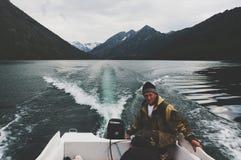 Ein Mann fährt ein Motorbootsegeln am Abend Lizenzfreies Stockbild