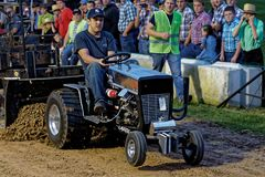 Ein Mann fährt an einem Rasen-Traktor-Zug lizenzfreie stockfotografie