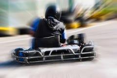 Ein Mann fährt gehen-kart mit Geschwindigkeit im Park Lizenzfreie Stockfotos