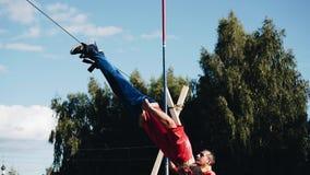 Ein Mann führt einen schwierigen Trick durch Rotation um die Achse auf dem Kabel Seine Beine werden am Seil gebunden stock video