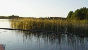 Ein Mann fischt von einem Boot auf Sonnenuntergang stock video footage