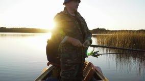 Ein Mann fischt von einem Boot auf Sonnenuntergang stock footage