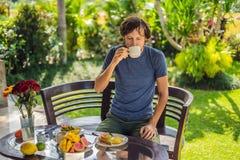 Ein Mann frühstückt auf der Terrasse stockfotos