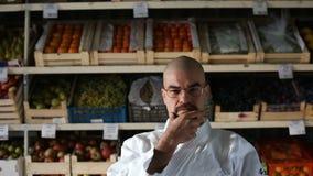 Ein Mann gegen den Hintergrund mit Gestellen mit Obst und Gemüse stock video
