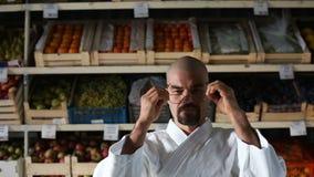 Ein Mann gegen den Hintergrund mit Gestellen mit Obst und Gemüse stock footage