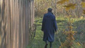 Ein Mann, gehend entlang die Straße im Dorf am Herbsttag Flacher Fokus stock video footage